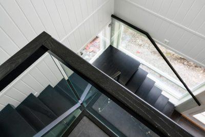 Tretrapp med glassrekkverk og håndløper i tre.